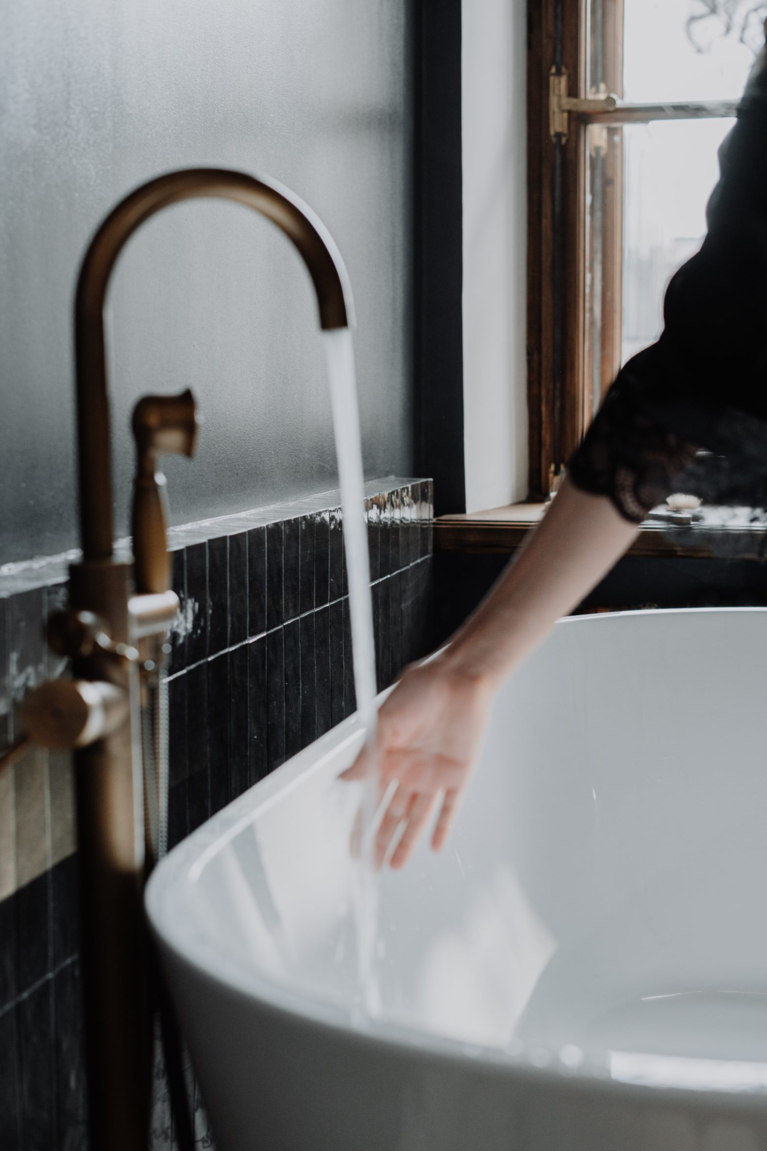 Woman's hand under running water from tub faucet