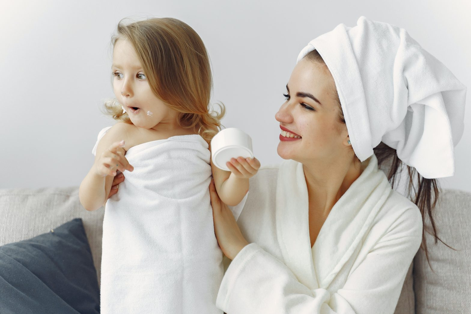 Mother and young daughter in robes and towels, smiling and playing after bath.
